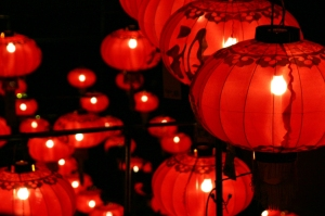 Dozens of round red Chinese lanterns lit against a black background