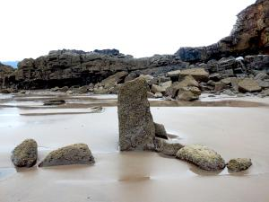 Vertival stone in sand with tide outon