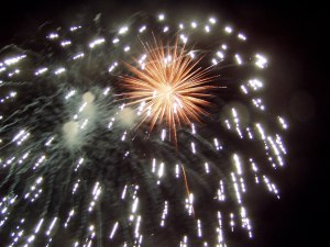 Large white fireworks burst in front of small gold burst