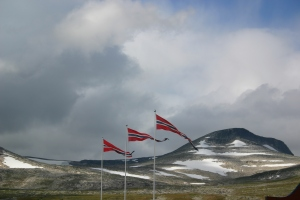Flags blowing against background of snowy hill and sky