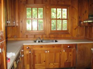 Kitchen window in kitchen with natural wood walls and cabinets