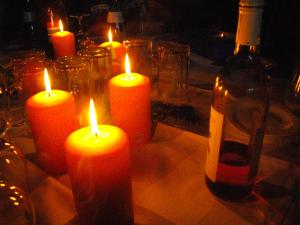 Three lit pillar candles and an empty wine bottle in the dark