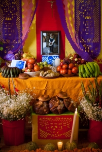 Elaborate ofrenda for a man in Milpa Alta Mexico coverd in an oranges clotht with offerings of bamaas, apples and other fruit