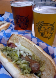 Two glasses of beer with wurst and condiments on hot dog stly bun