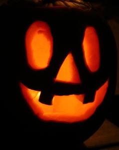 Orange light of jack o lantern against pumpkin in dark
