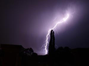 Lightning strike in dark sky behind tower od building