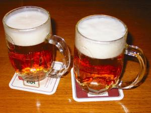 Two mugs of beer with foam on top