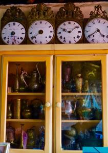 Row of clockk faces shwing different times on top of glass doored cabinet full of kitchen things
