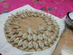 large round platter with three rings of jiaozi on it