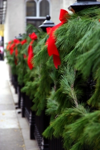 Pine garland with red bows on a wrought iron fence