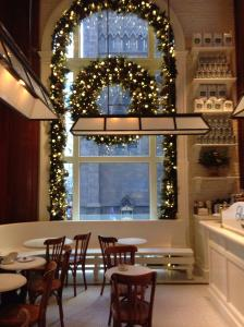 Large two story window decorated with a wreath and garland of greens and small lights