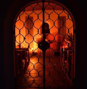Candlelit church interior through iron grill gates