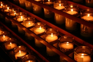 Rows of lit candles in a stand