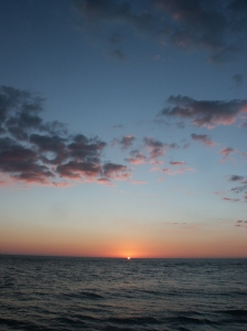 Sun just coming over the horizon on the ocean in twilight