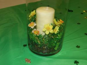 Glass with large white candle surrounded by small yellow flowers on green tablecloth