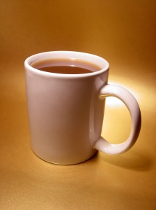 White mug containing milky tea.