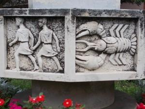 : Well with train and Astrological sign reliefs. - Korond, By Globetrotter19 [CC BY-SA 3.0 (https://creativecommons.org/licenses/by-sa/3.0)], from Wikimedia Commons Gyártelep neighborhood, [[:en:Dunakeszi|Dunakeszi]], [[:en:Pest County|Pest County]], [[:en:Hungary|Hungary]].}}{{hu|1=: AD tranz MÁV DVJ Kft. főbejárati épület előtt levő tér, azonosító -4950. A gyár már a Bombardier-é (2010). A tér közepén a vasúti motívumokkal díszített kút (Ispánki József, 1972). A medencerészen körbe a tizenkét csillagjegyet látni rajta. - [[:hu:Pest megye|Pest megye]], [[:hu:Dunakeszi|Dunakeszi]], Gyártelep városrész, Korond{{Monument Hungary|-4950}}