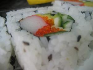 Close up of sushi segment, rice on outside