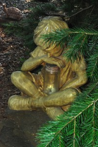 Small statue of child holding jar of fireflies