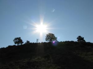 Bright white sun over hillscape