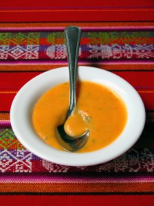 White rimmed bowl of bright orange creamed soup