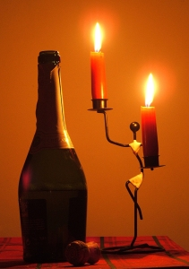 Lit red candles on candelabra next to champagne bottle