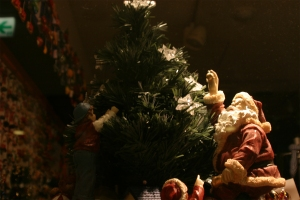 Seated Santa figurine next to Christmas treee