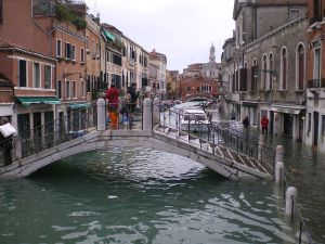 Overflowing canal and flooded bridge in Venice Italy