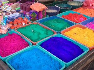 Tubs of blue turquoise, yellow and pink color powders for Holi festival