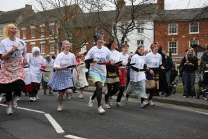 Women in headscarves and arons running with frypans in a pancake race