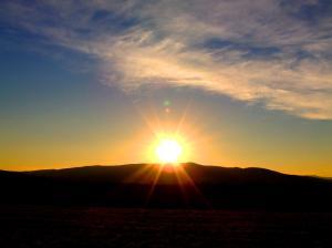 Sunset over darkened hill