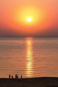 red setting sun above red tinted ocean