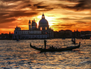 Venic sunset behind the basilica & gondola on the water in foreground