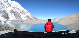 Nepali man looking out at the Himalayas seen from behind him sitting
